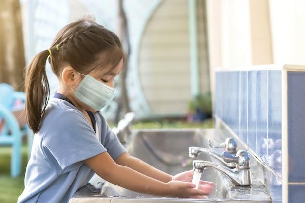 Szczęśliwy azjatycki dzieciak myje ręce po zabawie na świeżym powietrzu z maską, gdy wraca do szkoły po spadku pandemii koronawirusa