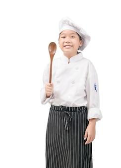 Szczęśliwy azjatycki dziewczyna kucharz w mundurze trzymając drewnianą łyżkę na białym tle