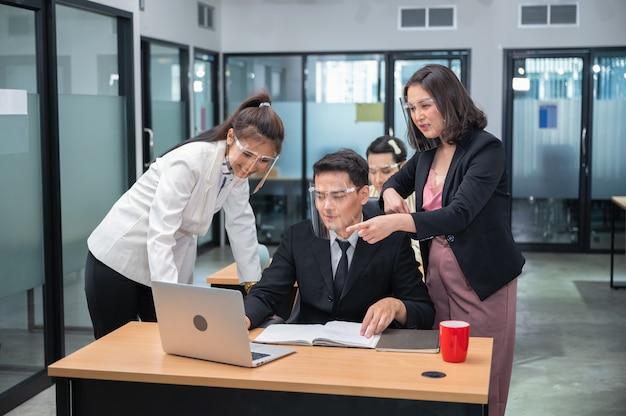 Szczęśliwy azjatycki kierownik kobieta doradza i współpracuje z kolegami pracującymi z laptopem przy biurku w biurze