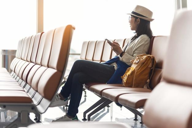 Szczęśliwy azjatycki kobieta podróżnik cieszy się z smartphone.