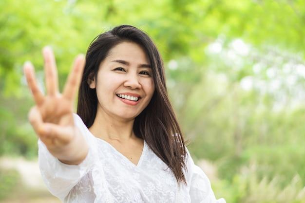 Szczęśliwy azjatycki kobieta seansu palec starzeje się 30 lat