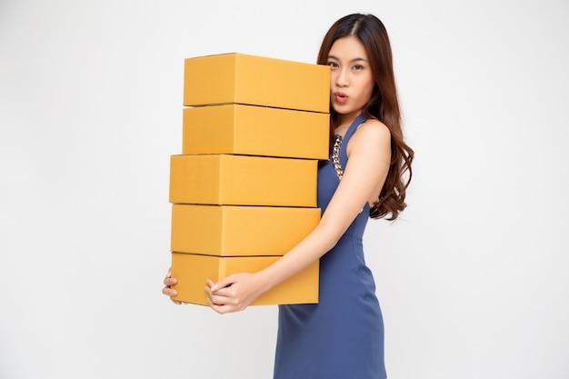 Szczęśliwy azjatycki kobiety mienia pakunku pakuneczka pudełko, doręczeniowy kurier i wysyłki usługa pojęcie