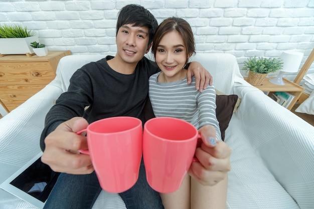 Szczęśliwy azjatycki kochanek ściska filiżankę wody i trzyma