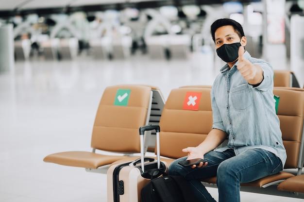 Szczęśliwy azjatycki mężczyzna podróżnik noszący maskę na twarz siedzący na krześle dystansowym pokazując kciuk do góry