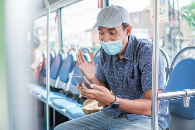 Szczęśliwy azjatycki mężczyzna wiwatujący świętujący patrząc na smartfona w publicznym autobusie z maską