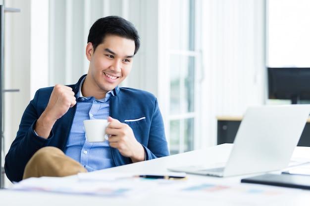 Szczęśliwy azjatycki młody biznesmen zobaczyć udany biznes plan na komputerze przenośnym