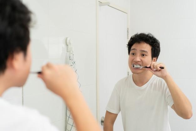Szczęśliwy azjatycki młody człowiek w biały t-shirt szczotkowanie zębów w łazience rano. mężczyzna przygotowujący się i sprawdzający twarz i ciało przed pójściem do pracy. rutynowa aktywność w życiu codziennym.