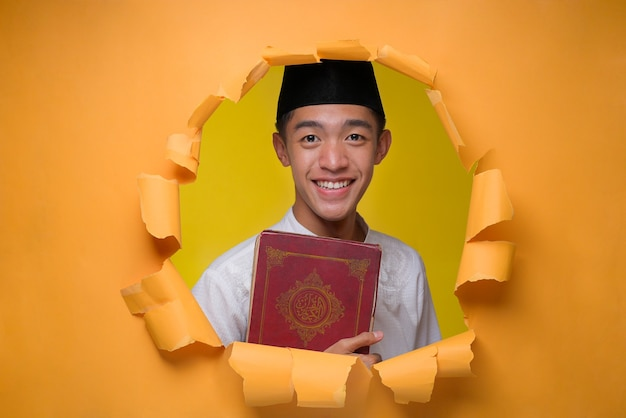 Szczęśliwy azjatycki muzułmanin trzymający święty koran, ubrany w muzułmański materiał z czapką, pozuje przez rozdarty żółty papierowy otwór, czytanie koranu podczas ramadanu kareem