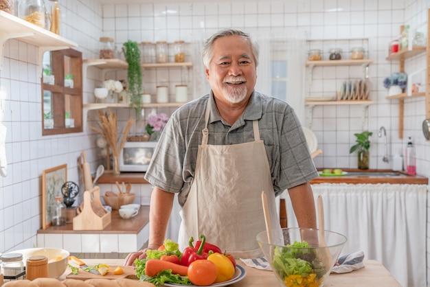 Szczęśliwy azjatycki starszy mężczyzna nosi fartuch śniadanie gotowanie w kuchni w domu.