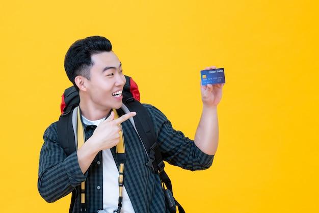 Szczęśliwy azjatycki turystyczny backpacker ono uśmiecha się i wskazuje karta kredytowa