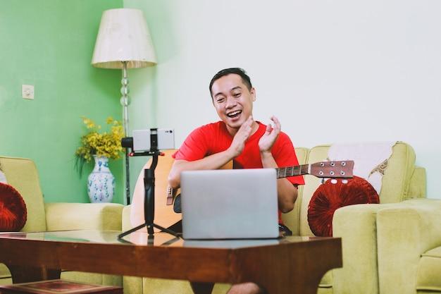 Szczęśliwy azjatycki youtuber lub muzyk wchodzący w interakcję z publicznością poprzez oklaski