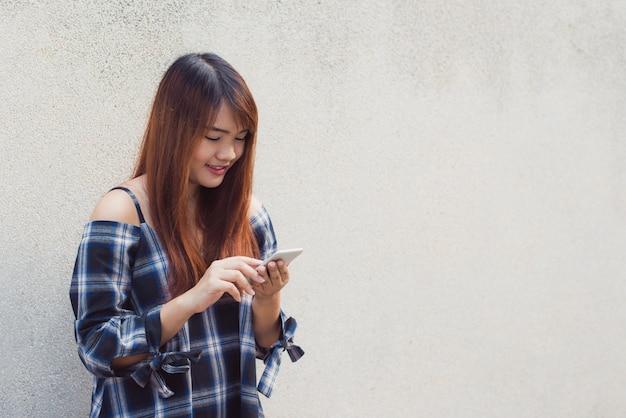 Szczęśliwy azjatyckich kobieta przy użyciu smartphone na szarym tle. obrazy stylu efektów klasycznych.