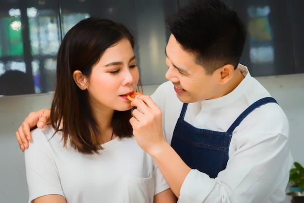 Szczęśliwy azjatyckich par szefa kuchni, gotowanie w kuchni.
