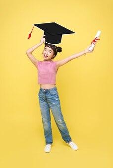 Szczęśliwy azjatyckich słodkie uczennica z kapeluszem ukończenia szkoły i dyplomem na białym tle na żółtym tle.