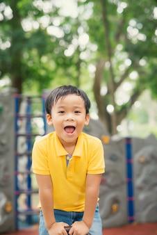Szczęśliwy azjatyckie dziecko bawiąc się na huśtawce. śliczny chłopiec dziecko ćwiczenia na sprzęcie do zabawy i radości. on uśmiechnięty show szczęśliwy i zabawny bawić się na placu zabaw dla dzieci w społeczności.