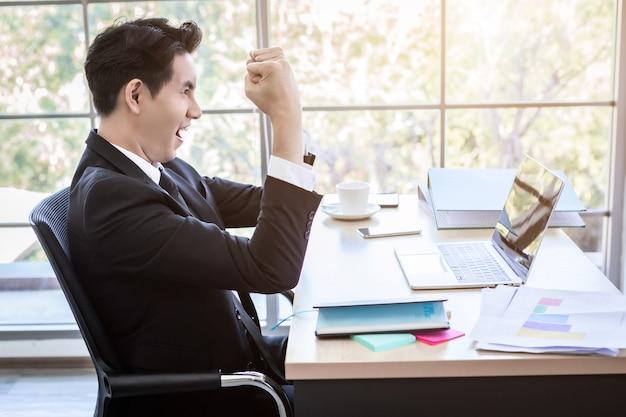 Szczęśliwy azjatyckiego młodego biznesmena widzę udany biznesplan na laptopie i długopis na tle drewnianego stołu w biurze, biznes wyraził zaufanie embolden