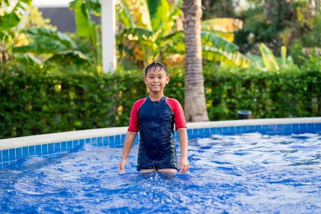 Szczęśliwy azjatykci dzieciak chłopiec dopłynięcie na pływackim basenie w lecie