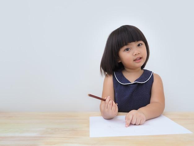 Szczęśliwy azjatykci dzieciak dziewczyny rysunek z barwionym ołówkiem.