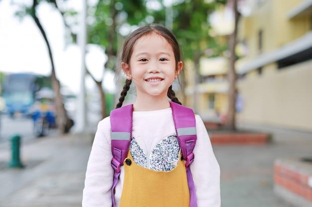 Szczęśliwy azjatykci dziecko dziewczyny odprowadzenie z schoolbag