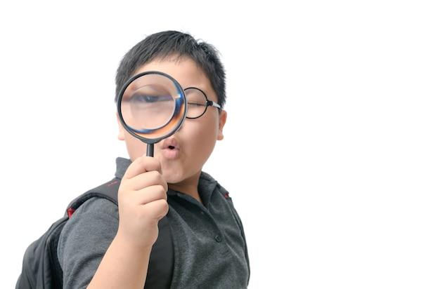Szczęśliwy azjatykci gruby chłopiec mienia powiększać - szkło.