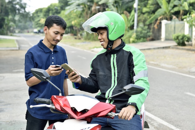 Szczęśliwy azjatykci mężczyzna rozkazuje motocyklu taxi telefonem komórkowym