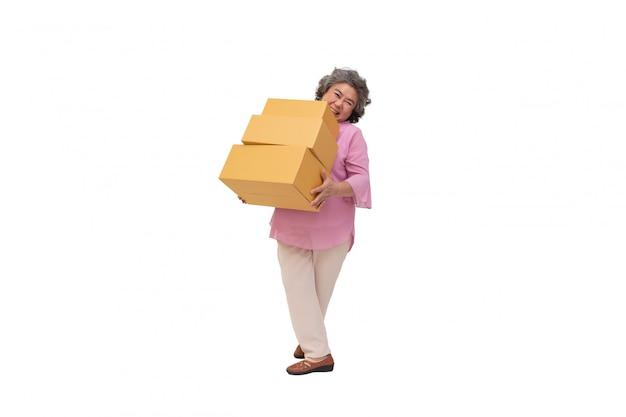 Szczęśliwy azjatykci starszy kobiety mienia pakunku pakuneczka pudełko odizolowywający na biel ścianie, doręczeniowym kurierze i wysyłki usługowym pojęciu ,.
