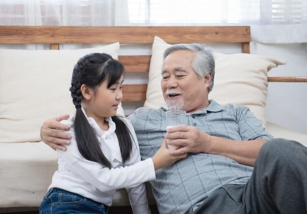 Szczęśliwy azjatykci starszy starszy dziad wnuka spojrzenie i opiekuje się z dawać mleku i całować na policzku podczas gdy siedzący na kanapie w domu, emerytura zdrowie stylu życia pojęcie.