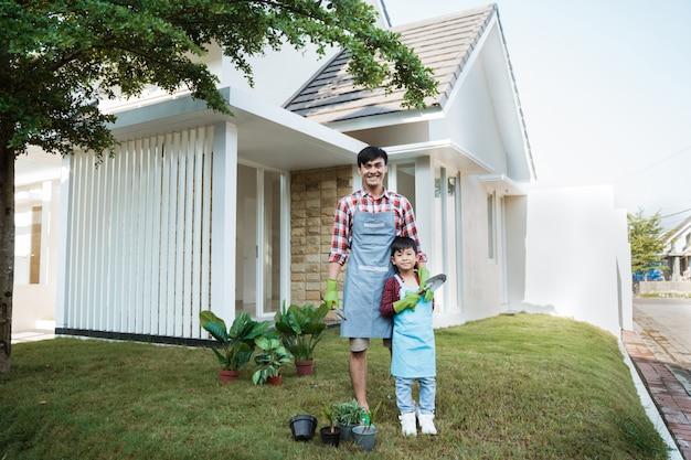 Szczęśliwy azjatykci tata i syna ogrodnictwo przy jego domem uprawia ogródek