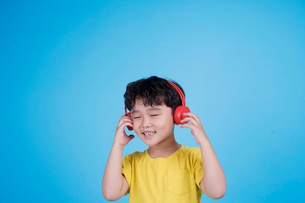 Szczęśliwy azji mały chłopiec ze słuchawkami słuchać muzyki