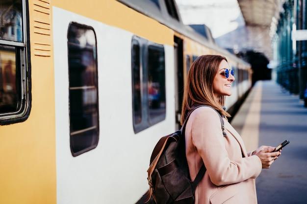 Szczęśliwy backpacker kaukaski kobieta na peronie na stacji kolejowej przy użyciu telefonu komórkowego. koncepcja podróży