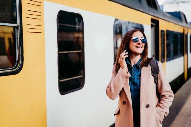 Szczęśliwy backpacker kaukaski kobieta na peronie na stacji kolejowej rozmawia przez telefon komórkowy. koncepcja podróży