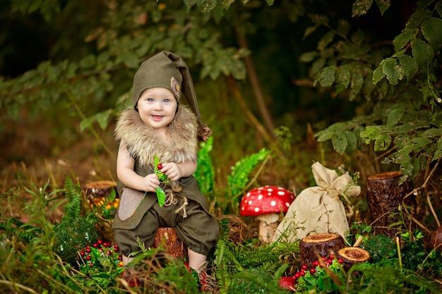 Szczęśliwy bajkowy gnom chłopiec bawi się i spaceruje po lesie, zbiera grzyby, je jabłka