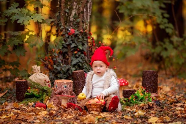 Szczęśliwy bajkowy leśny krasnal bawi się i spaceruje po lesie, zbiera i zjada pyszne jabłka