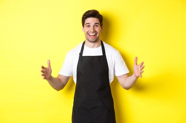Szczęśliwy barista trzymający coś dużego, kształtujący duży przedmiot, stojący na żółtym tle.