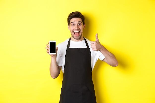 Szczęśliwy barista w czarnym fartuchu pokazuje ekran smartfona, zrób kciuk, polecając aplikację kawiarnianą, stojąc na żółtym tle.