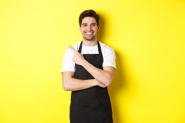 Szczęśliwy barista wskazujący palec w lewo i uśmiechnięty ubrany w czarny fartuch, stojący na tle żółtego b...