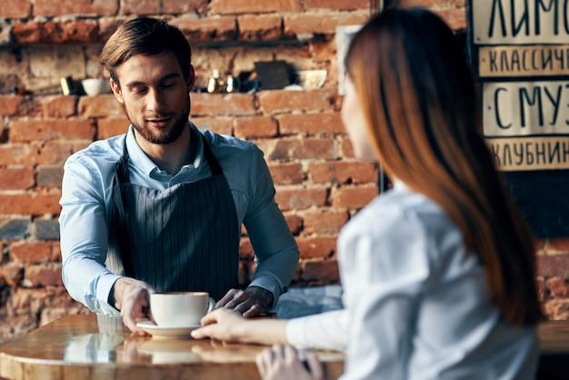 Szczęśliwy barman serwujący filiżankę kawy pacjentowi w kawiarni pić wnętrze ceglanego muru