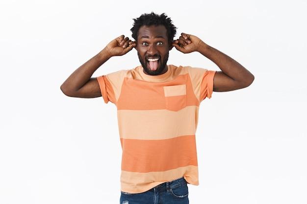 Szczęśliwy, beztroski, brodaty afro-amerykanin dobrze się bawi, nie boi się bycia zabawnym i uroczym