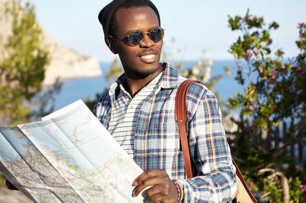 Szczęśliwy, beztroski młody afroamerykanin z plecakiem w lustrzanych soczewkach i nakryciu głowy, planujący następny przystanek podczas podróży, czytający papierową mapę w dłoniach, stojący w pięknym krajobrazie