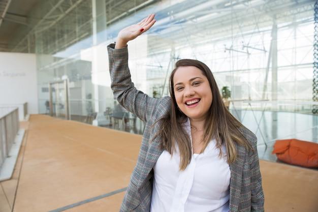 Szczęśliwy biznes kobieta macha ręką na zewnątrz