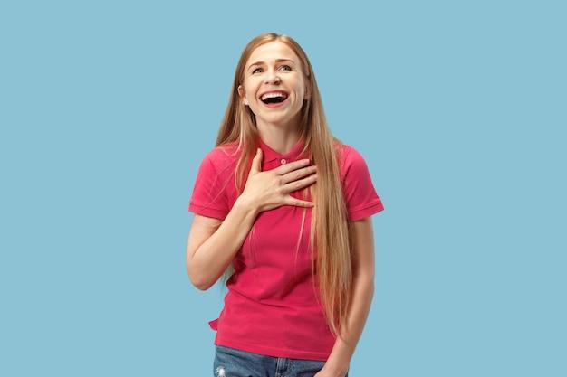 Szczęśliwy biznes kobieta stojąc i uśmiechając się na białym tle na niebieskim studio