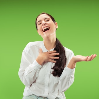Szczęśliwy biznes kobieta stojąc i uśmiechając się na białym tle na zielonej ścianie. piękny portret kobiety w połowie długości. młoda kobieta emocjonalna. ludzkie emocje, koncepcja wyrazu twarzy
