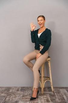 Szczęśliwy biznes kobieta stojąc na białym tle nad szarym tle ściany wyświetlono porządku gest.