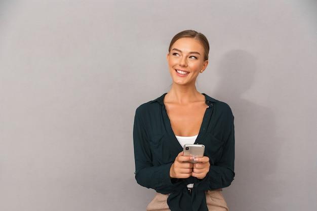 Szczęśliwy biznes młoda kobieta pozowanie na białym tle nad szarym tle ściany za pomocą telefonu komórkowego.