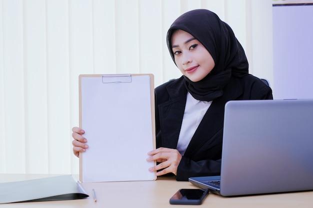 Szczęśliwy biznes młoda kobieta trzyma finansowo dokument w biurze