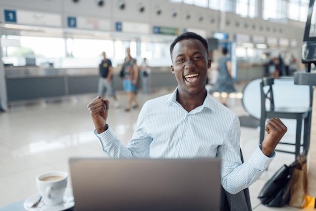 Szczęśliwy biznesmen afro siedzi na laptopie w salonie samochodowym. przedsiębiorca odnoszący sukcesy na targach motoryzacyjnych, murzyn w formalnym stroju, salon samochodowy