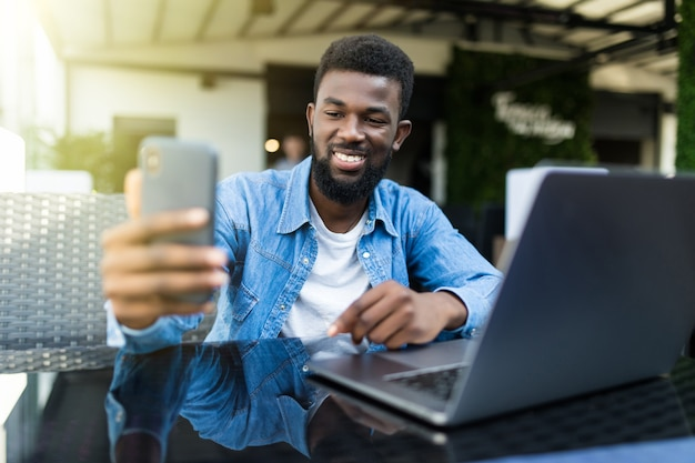 Szczęśliwy biznesmen afroamerykański przy selfie w kawiarni
