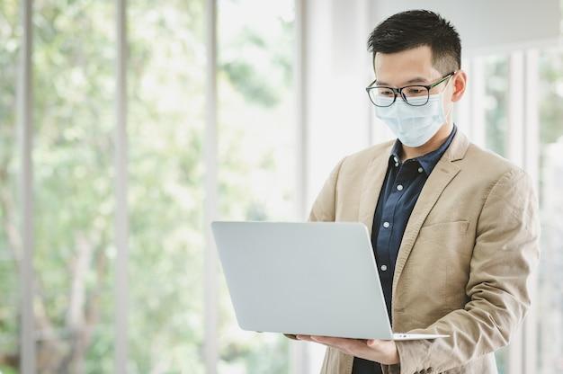 Szczęśliwy biznesmen azjatyckich przedsiębiorca nosi maskę stojącą i trzymając laptopa z przekonaniem w sali konferencyjnej w nowoczesnym biurze
