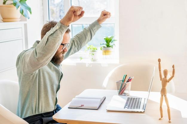 Szczęśliwy biznesmen czuje podniecenie, podnosząc pięści, patrząc na laptopa otrzymuje dobre wieści, osiąga cele życiowe, świętuje sukces biznesowy, wykonuje gest zwycięzcy. pojęcie sukcesu i osiągnięcia celu.