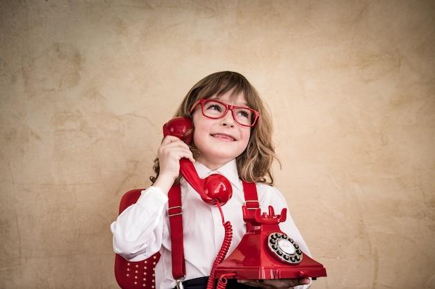 Szczęśliwy biznesmen dziecko z retro telefonem. komunikacja w koncepcji biznesowej